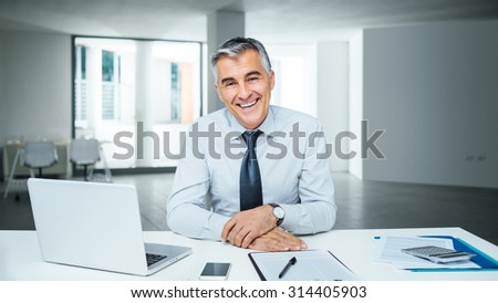 Confident handsome businessman sitting at office desk and smiling at camera - stock photo