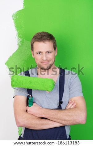 Confident handsome friendly young painter standing with folded arms holding a roller in front of a half painted green wall - stock photo