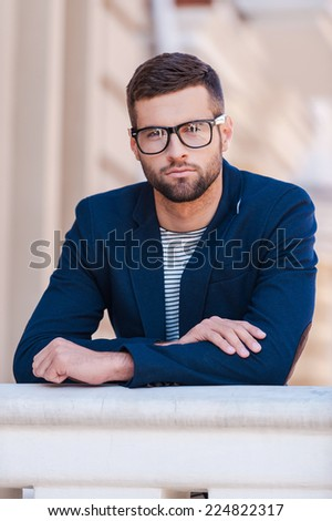 Confident handsome. Handsome young man in eyeglasses and smart casual wear looking at camera while standing outdoors - stock photo