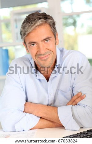 Confident handsome man with arms crossed - stock photo