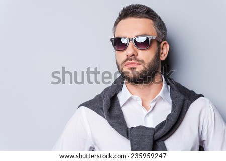 Confident handsome. Portrait of handsome young man in sunglasses and smart casual wear looking away while standing against grey background - stock photo