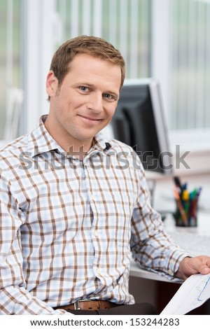 Confident handsome successful businessman relaxing in his chair at the office giving the camera a friendly smile - stock photo