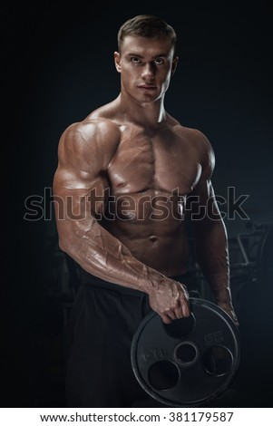 Confident handsome young athletic man doing exercises with barbell plate. Muscular body on dark background. Fitness sports. Healthcare, bodycare and physique concept. - stock photo