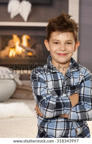 Confident happy little boy standing arms crossed in living room, smiling, looking at camera. - stock photo