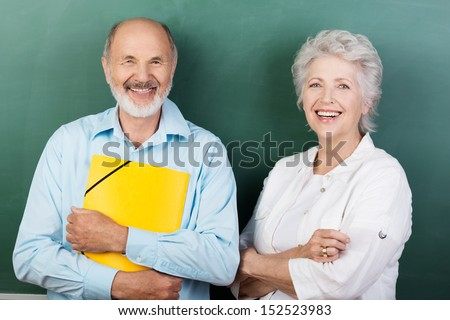 Confident happy senior couple standing with folded arms clutching a bright yellow folder - stock photo