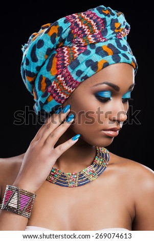 Confident in her perfect look. Beautiful African woman wearing a headscarf and necklace looking away and touching her face while standing against black background - stock photo