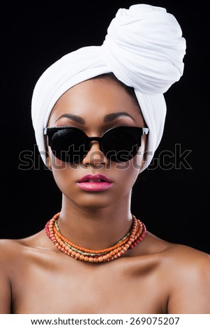 Confident in her style. Beautiful African woman wearing a headscarf and looking at camera while standing against black background - stock photo