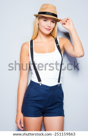 Confident in her style. Beautiful young blond hair women adjusting her hat while standing against grey background   - stock photo