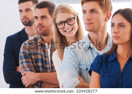 Confident in her team. Attractive young woman smiling while standing in a row with other people  - stock photo