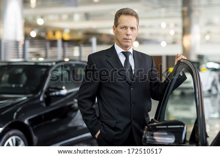 Confident in his choice. Confident grey hair man in formalwear holding hand on opened car door and looking at camera - stock photo