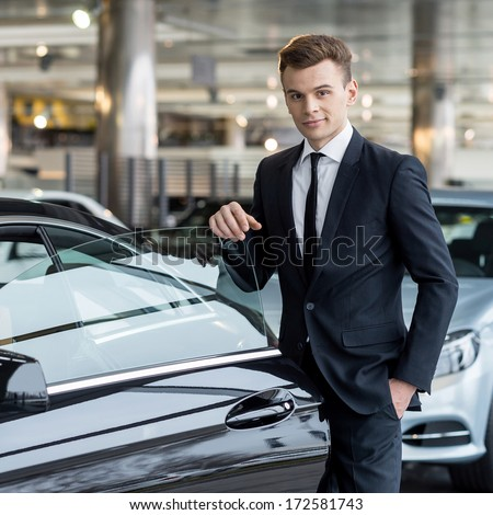 Confident in his choice. Confident young man in formalwear leaning at the car door and looking at camera while standing at car dealership - stock photo