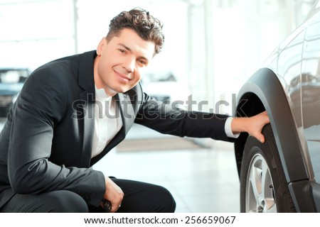 Confident in his choice. Smiling handsome man in suit checking wheels in a new car and smiling at camera in car dealership  - stock photo