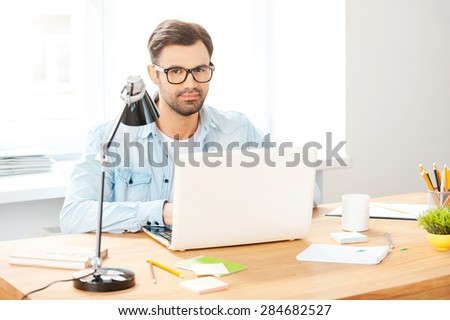 Confident in his job. Handsome young man in shirt and eyewear working on laptop while sitting at his working place - stock photo
