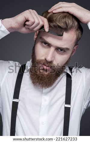 Confident in his perfect style. Confident young bearded man combing his hair and looking at camera while standing against grey background - stock photo