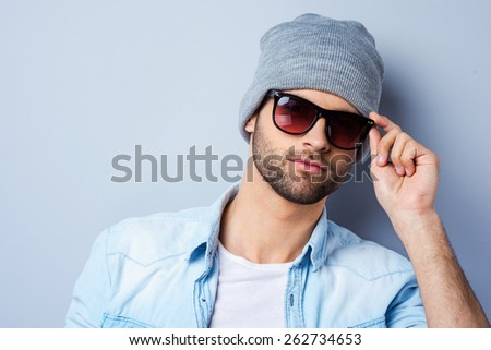 Confident in his perfect style. Handsome young fashionable man adjusting his sunglasses and looking at camera while standing against grey background - stock photo