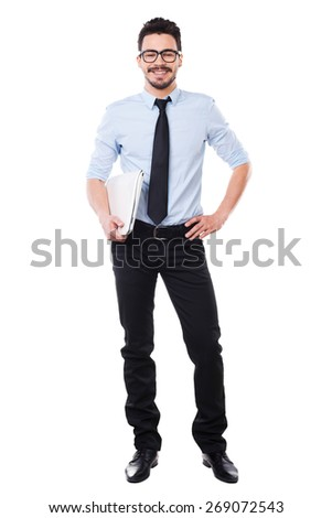 Confident in his qualification. Full length of handsome young man in shirt and tie holding laptop and smiling while standing against white background - stock photo