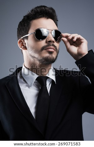 Confident in his style. Handsome young man in formalwear adjusting his sunglasses and looking away while standing against grey background - stock photo