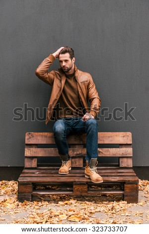 Confident in his style. Handsome young man sitting on the wooden pallet and adjusting his hair with grey wall in the background and orange fallen leaves on the floor  - stock photo