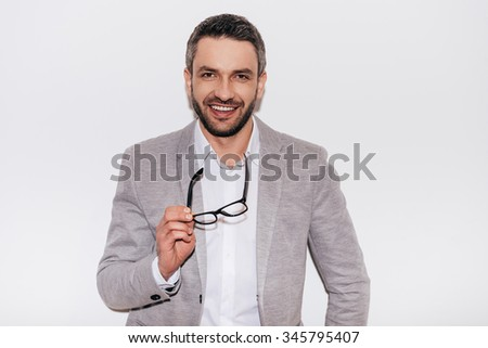 Confident in his success. Confident mature man carrying eyeglasses and looking at camera with smile while standing against white background - stock photo
