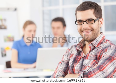 Confident in his team. Cheerful young man in glasses looking at camera and smiling while his colleagues working on the background - stock photo