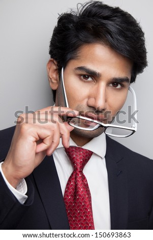 Confident Indian businessman taking of glasses - stock photo