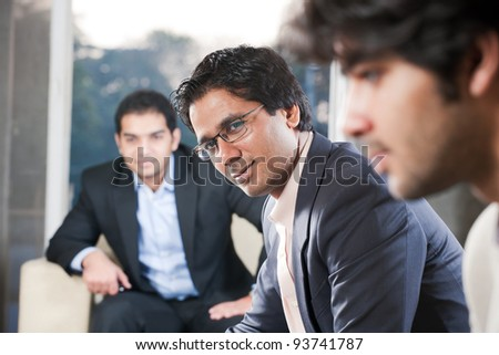 confident indian businessman with his colleagues in the background - stock photo