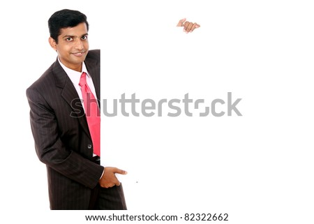 Confident Indian young businessman posing with white board - stock photo