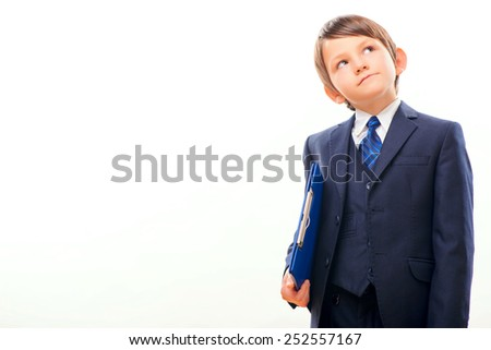 Confident little leader. Thoughtful little boy in formalwear holding a blue clipboard and looking up while standing isolated on white background with copy space - stock photo