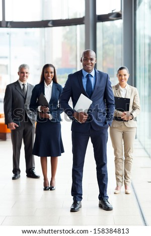 confident male african business leader and team in office - stock photo