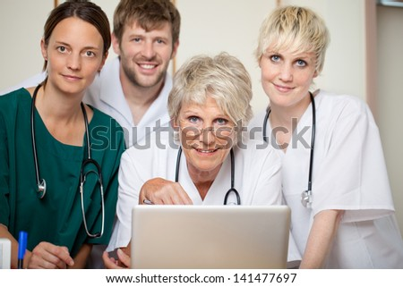 Confident male and female doctors with laptop in hospital - stock photo