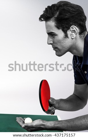 Confident male athlete playing table tennis against grey background - stock photo