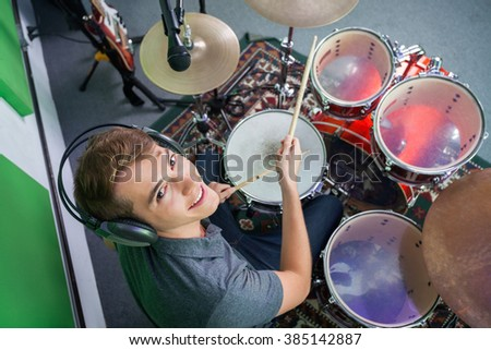 Confident Male Drummer Wearing Headphones While Performing - stock photo