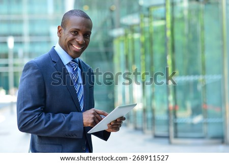 Confident male entrepreneur posing with digital tablet  - stock photo
