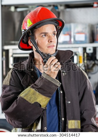 Confident male firefighter looking away while using walkie talkie at fire station - stock photo