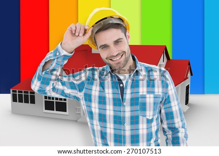 Confident male technicial wearing hard hat against digitally generated house - stock photo