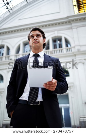 Confident man holding digital tablet computer while standing in big light hall of railway station,successful businessman on way to work reading news on his touch pad, pensive entrepreneur looking away - stock photo