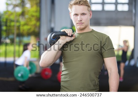 Confident man with kettlebell at fitness gym - stock photo