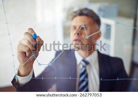 Confident man writing graph - stock photo
