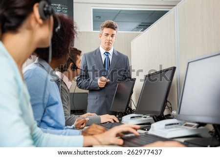 Confident manager instructing customer service representatives in office - stock photo