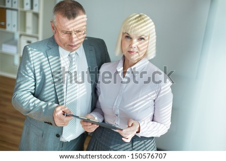 Confident mature businessman looking at document while his colleague looking at camera - stock photo