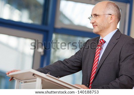 Confident mature businessman looking away while standing at podium in office - stock photo