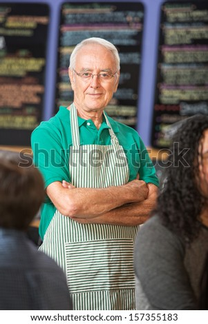 Confident mature Caucasian male with folded arms - stock photo