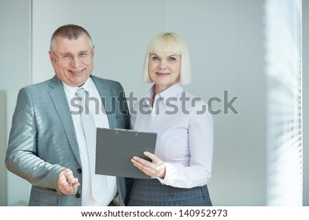 Confident mature co-workers looking at camera with smiles - stock photo