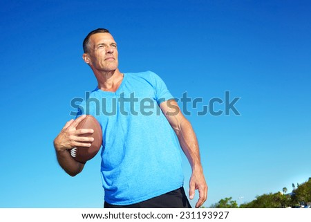 Confident mature man holding American football against clear blue sky - stock photo