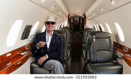 Confident mature man sitting at his seat in private airplane and smiling - stock photo