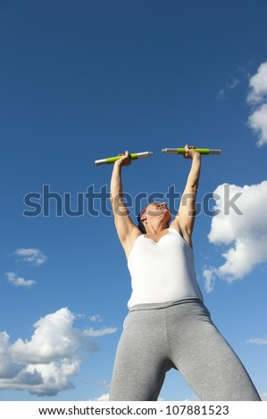 Confident mature woman exercising with weights outdoor, isolated with blue sky as background and copy space. - stock photo