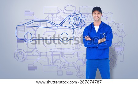 Confident mechanic holding wheel wrenches against grey vignette - stock photo