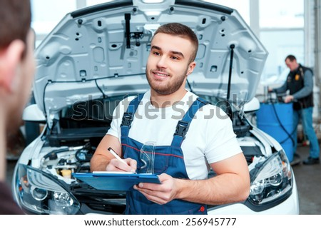 Confident mechanic. Portrait of a handsome car mechanic speaking with his client and putting information in his clipboard in the car repair station - stock photo