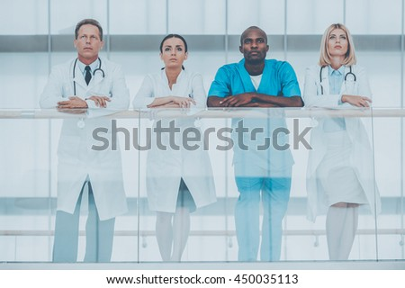 Confident medical team. Low angle view of four confident doctors standing close to each other and looking away while leaning at the handrail - stock photo