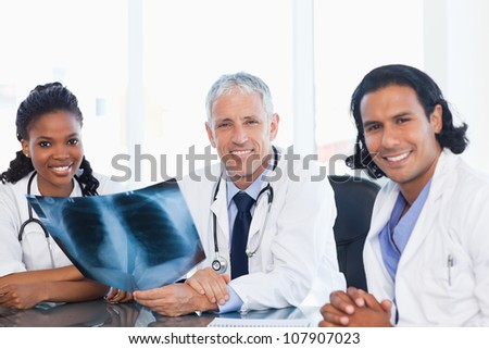 Confident medical team smiling while working hard with a patient's x-ray - stock photo